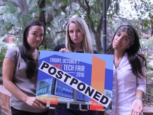 Photo of IT-Communications staff looking sad and holding a 2016 Tech Fair poster with the word 'POSTPONED' taped to it.