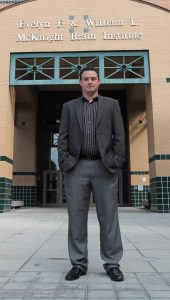 Photo: Asst. Professor Adam Woods in front of the McKnight Brain Institute