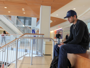 PHOTO: Male student using his smartphone inside Reitz Union.