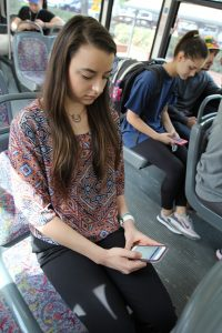 PHOTO: Female student using UF mobile print app while riding RTS bus to campus.