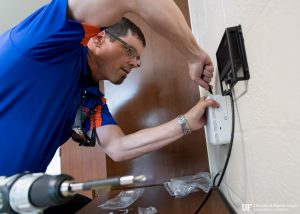 PHOTO: UFSA-IT staff member installing wireless access point in a resident's room in Broward Hall.