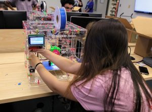 PHOTO: Female undergraduate learning to build a 3-D printer.