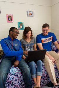 PHOTO: Three students siting inside UF Hume Hall, looking at a laptop