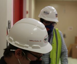 PHOTO: Two UFIT employees in hard hats, working inside the UF Data Center