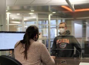 PHOTO: Help Desk representative assisting student in 132 Hub. Photo taken in Jan. 2021.