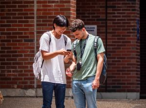 PHOTO: Two male students look at a smartphone on campus